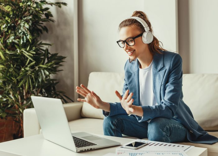Cheerful young female in casual outfit and glasses having video conversation with colleagues and sharing business ideas while sitting on couch in modern workplace