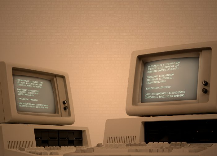 Vintage technology beige background with two old computers showing binary code on its monitor. Code spreads across image area. Retro revival of seventies devices. Plenty of copy space on the side. Low-key background for easy costumization.